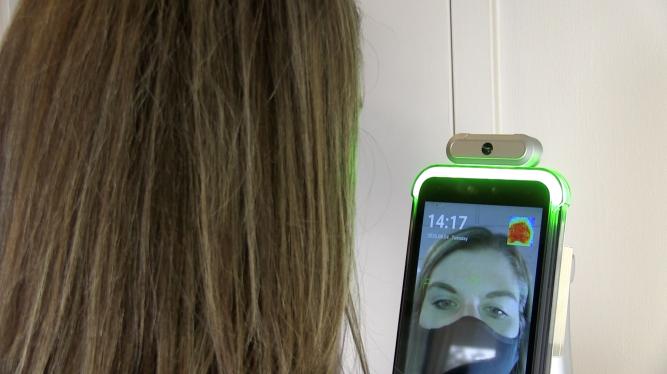 Masked patient checks temperature using a PDi temperature scanner