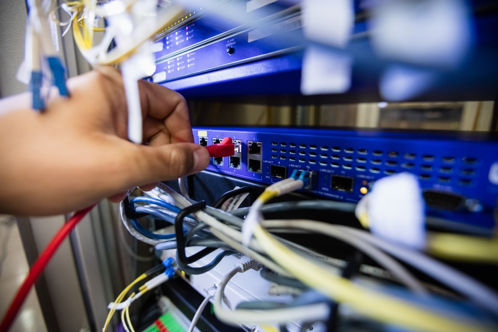 Close-Up of technician fixing patch cable in a rack mounted server
